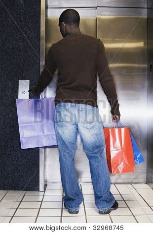 African man waiting for elevator with shopping bags