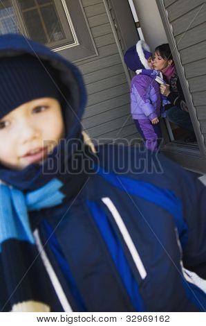 Mother sending children to school in winter