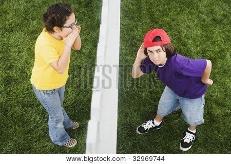 Menina de raça mista gritando para menino através de cerca