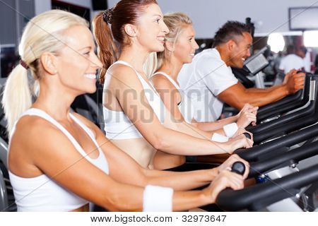 group of people cycling in gym