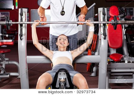 fitness woman lifting barbell in gym with personal trainer's help