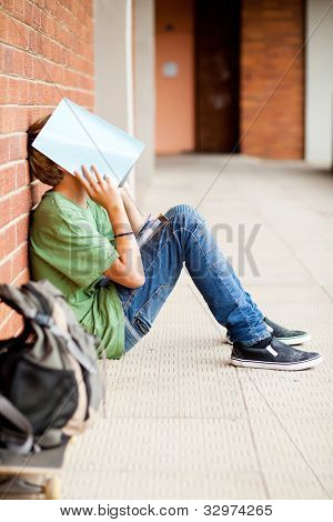 frustrated high school boy using book cover his face in school passage