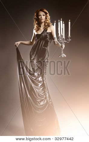 Fashion shoot of beautiful woman in a long dress over dark background (WARNING! There is some noise on the image)