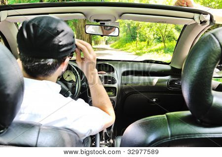 Portrait of a man putting sunglasses on his eyes in a car
