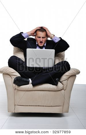 Businessman having headache while sitting in front of his laptop