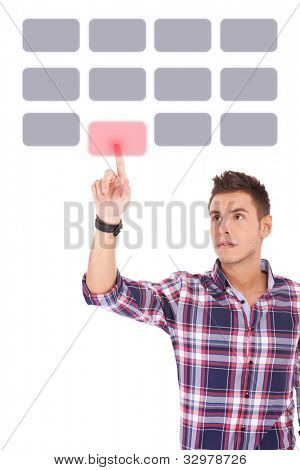 young casual man making a selection by pushing a button