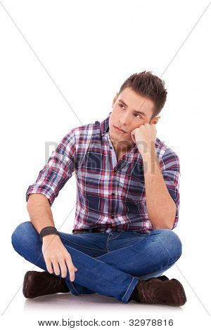 seated young man thinking and looking a little sad, over white background