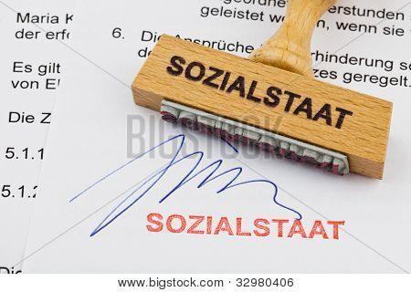 a stamp made of wood lying on a document. german words: welfare