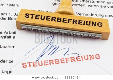 a stamp made of wood lying on a document. german words: exemption