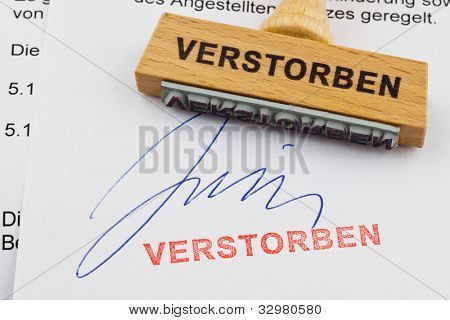 a stamp made of wood lying on a document. german inscription: died