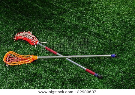 A pair of lacrosse sticks laying on a field