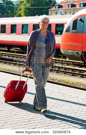 mature vital elderly couple at the railway station. travel on holiday