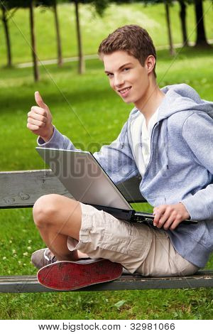 a teenager with a laptop outdoors. sitting in the park mobile internet