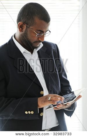 Homem americano Africano bonito com computador tablet