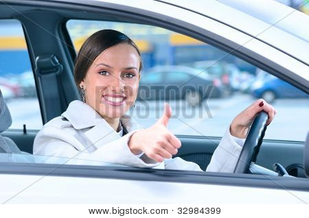 happy woman is showing a thumb from a car