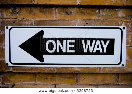 One Way Sign Against A Brick Wall
