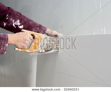 cutting plasterboard plaster hand with grunge dirty saw