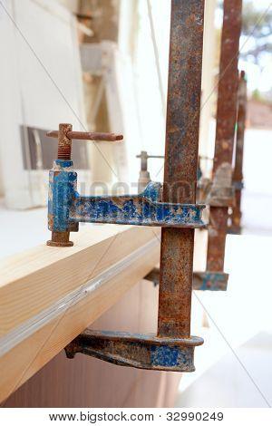 Carpenter screw clamp tools pressing wood slats ang white glue