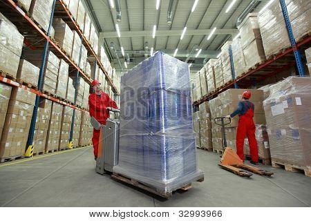 Lagerhaltung - zwei Arbeiter in Uniformen und Schutzhelme arbeiten im Lagerhaus