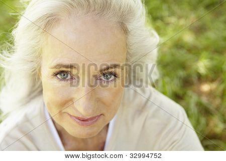 Senior woman sitting on grass