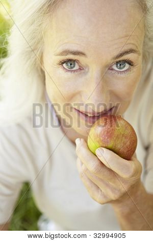 Senior woman eating apple outdoors