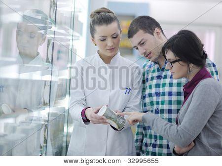 joven farmacéutico sugiriendo drogas médicas al comprador en Droguería Farmacia