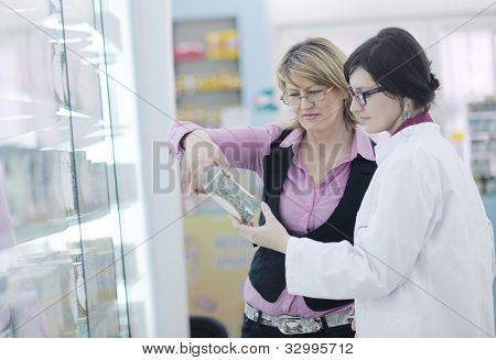 young pharmacist suggesting medical drug to buyer in pharmacy drugstore