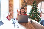Beautiful woman sitting at the table working with laptop at home around christmas tree clapping and  poster