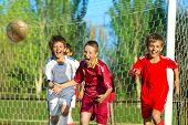 picture of offensive  - Little Boys playing soccer on the sports field next to goal - JPG