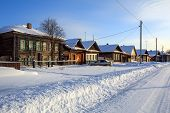 Snow-covered Village Street In Winter. View Of The Traditional Wooden Houses On A Sunny Winter Day.  poster