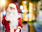 Middle age handsome man wearing Santa Claus costume and beard standing Looking fascinated with disbe poster