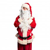 Middle age handsome man wearing Santa Claus costume and beard standing afraid and shocked, surprise  poster