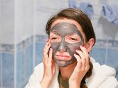 The Girl In The Face Mask Looks In The Mirror Displeased. Cosmetic Black Mask. Woman Brings Beauty T poster