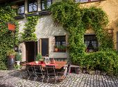 Romantic street cafe decorated with climbing plants on Romantic Road touristic route in Bavaria, Ger poster