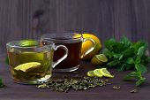 Healthy Lifestyle. Cups Of Green And Black Tea With Lemon And Leaves Of Green Mint On Wooden Backgro poster