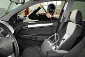 stock photo of theft  - A thief wearing a robbery mask trying to steal a purse bag in a automobile - JPG