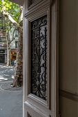 Opened Door With Ornate Antique Grating On Door Window. Blurry Background With City Street. Beige Pa poster