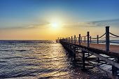 Bright And Colorful Sunrise Over The Pier And Sea. Perspective View Of A Wooden Pier On The Sea At S poster