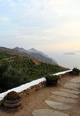 Greece, The Island Of Sikinos. A Paved Walkway Leading To A Winery. Views Over Mountain Slopes And F poster