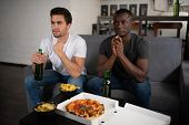 Anxious Multiracial Men Watching Football Match At Home poster