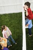 picture of peeping tom  - Mixed Race boys looking over fence at girls - JPG