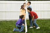 picture of peeping-tom  - Mixed Race children looking at each other through fence - JPG