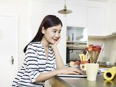 Beautiful Young Asian Woman Working From Home Sitting At Kitchen Counter Using Laptop Computer poster