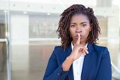 Serious Silent Professional Keeping Secret. Young Black Business Woman Standing At Outdoor Glass Wal poster