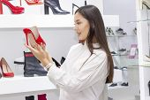 Girl Buys Shoes, A Boutique Selling Shoes. Beautiful Girl Is Shopping. On The Background Of A Girl S poster