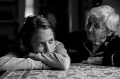 Old woman comforting a crying little girl granddaughter. Black-and-white photo. poster