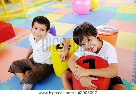Kinder spielen im neuen Spielplatz Kindergarten mit kleinen Anzahl Stühle