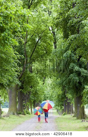 mother and her daughter with umbrellas in spring alley