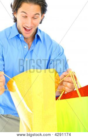 Excited Young Man Look At Shopping Bag