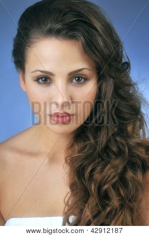Beautiful young brunette girl posing pretty to camera in the studio on blue background